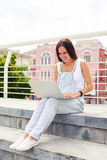 Pretty woman against city view working on her notebook computer Royalty Free Stock Photos