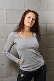 Pretty woman against the concrete wall Stock Images