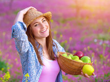Pretty woman with apples basket. Closeup portrait of pretty woman with apples basket, having picnic on pink floral meadow, harvest season, gardening concept Royalty Free Stock Images