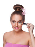 Pretty woman applying concealer with brush Stock Images