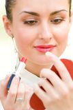 Pretty woman applying cosmetics Stock Photography