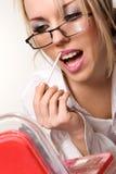 Pretty woman applying cosmetics. Sensual young woman applying cosmetics on her lips Stock Images