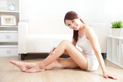 Pretty woman applying cream on her attractive legs. Beauty of young pretty woman with perfect shape and applying cream on her attractive legs indoors at home Royalty Free Stock Photography