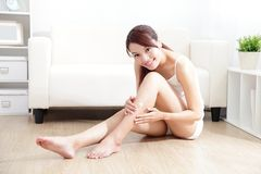 Pretty woman applying cream on her attractive legs. Beauty of young pretty woman with perfect shape and applying cream on her attractive legs indoors at home Stock Photo