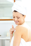 Pretty woman applying cream on her body Stock Images