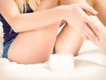 Pretty woman applying creme to her legs. Cute woman applying creme to her legs Royalty Free Stock Image