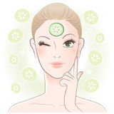 Pretty woman applying cucumber slice mask Stock Images