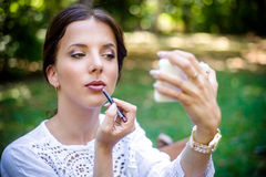 Pretty Woman Applying Lipstick at the Garden Stock Photo
