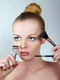 Pretty woman applying make up Stock Image