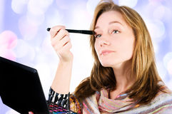 Pretty woman applying make up. Royalty Free Stock Photography