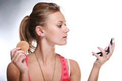 Pretty woman applying make-up Stock Photos