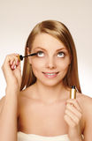 Pretty woman applying make up. Stock Photos