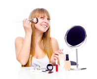 Pretty woman applying make up with brush Stock Photos