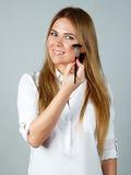 Pretty woman applying make up with brush Stock Image