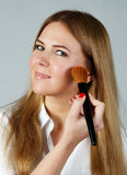 Pretty woman applying make up with brush Royalty Free Stock Images