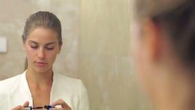 Pretty woman applying make up stock video