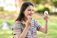 Pretty woman applying make-up with powder. At out Royalty Free Stock Photo