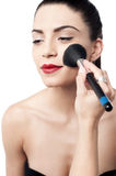 Pretty woman applying makeup with brush Stock Photo