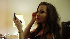 Pretty woman applying mascara to her eyelashes in front of small mirror. stock video footage