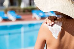 Pretty woman is applying sun cream on her shoulder before tanning by the pool. Sun Protection Factor in vacation, concept.  stock image