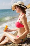 Pretty woman applying sunscreen lotion on her legs. Sexy woman is resting sitting on the sea cost with sun tan lotion sun drawing, summer time Stock Photography