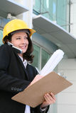 Pretty Woman Architect. A pretty woman architect holding blueprints and talking on the phone Stock Photography