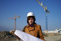 Pretty woman architect with blueprints and cranes Stock Photo