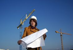 Pretty woman architect with blueprints and cranes Stock Image