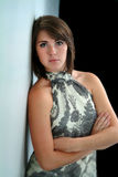 Pretty Woman with Arms Folded Leaning Against Wall Royalty Free Stock Image