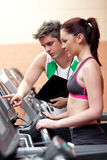 Pretty woman athlete standing on a running machine Stock Image