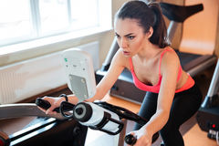 Pretty woman athlete working out on bicycle in gym royalty free stock images