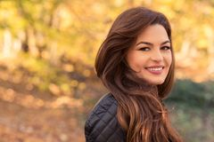 Pretty woman in the autumn forest. Smiling and feeling happy outdoors with copy text space area stock photos