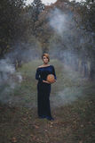 Pretty woman in autumn garden. She is holding a pumpkin Stock Photography