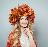 Pretty woman in autumn leaves crown. Happy model with makeup and curly hair, autumn portrait.  royalty free stock image