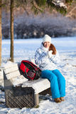 Pretty woman with backpack resting on bench in winter park Stock Photo