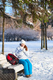 Pretty woman with backpack sits on a bench in winter park Stock Images