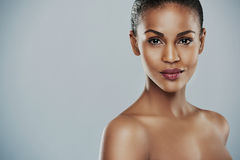 Pretty woman with bare shoulders with copy space. Front view of beautiful African female model with calm expression and bare shoulders over gray background with Royalty Free Stock Photo