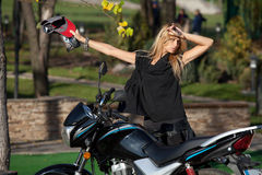 Pretty woman with a baseball cap near motorcycle Royalty Free Stock Photography