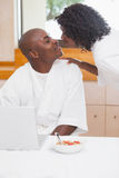 Pretty woman in bathrobe kissing partner at table Stock Photography