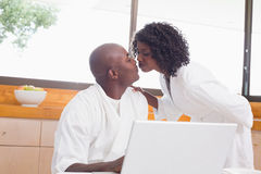 Pretty woman in bathrobe kissing partner at table royalty free stock images