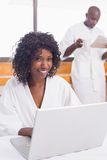 Pretty woman in bathrobe using laptop at table with partner in background Royalty Free Stock Image
