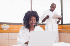 Pretty woman in bathrobe using laptop at table with partner in background Royalty Free Stock Images