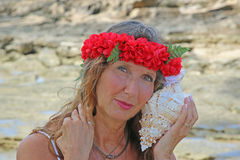 Pretty woman at beach. With lei headpiece and conch shell Stock Photos