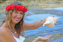 Pretty woman at beach. With lei headpiece and conch shell pouring water Royalty Free Stock Images