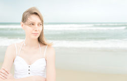 Pretty woman on beach looking somewhere. Pretty young woman on beach looking somewhere with thoughtful expression on face and hands crossed. Wind playing with Stock Photo