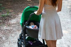 Pretty woman in beautiful dress holding the pram with her happy cute baby inside, mother and child pram walking outside royalty free stock images