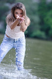 Pretty woman in the beautiful scenery at the river. Lady inside the river playing with the water, wearing white shirt and jean trouser. Pretty woman in the Royalty Free Stock Image