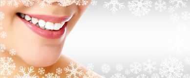 Pretty woman beauty smiling against a grey background. Pretty woman smiling against a grey background with copyspace and snowflakes. Christmas time concept royalty free stock image