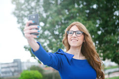 Pretty woman by becoming a photo with the phone Royalty Free Stock Photography