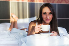 Pretty woman on bed with cup of coffee portrait, looking at camera, front look Stock Image